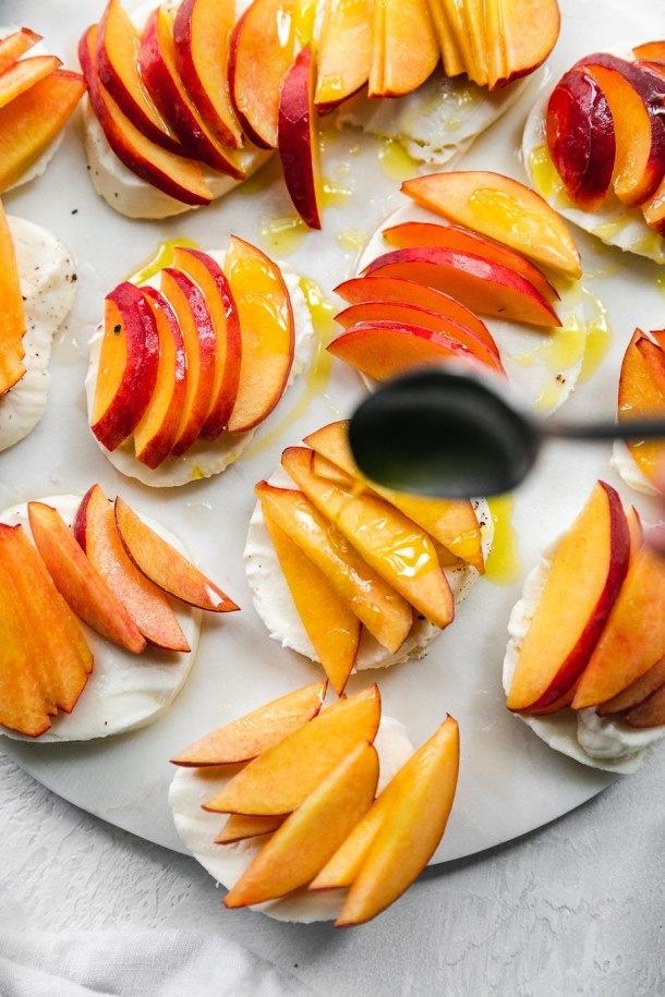 Overhead shot of sliced peaches and mozzarella being drizzled with olive oil