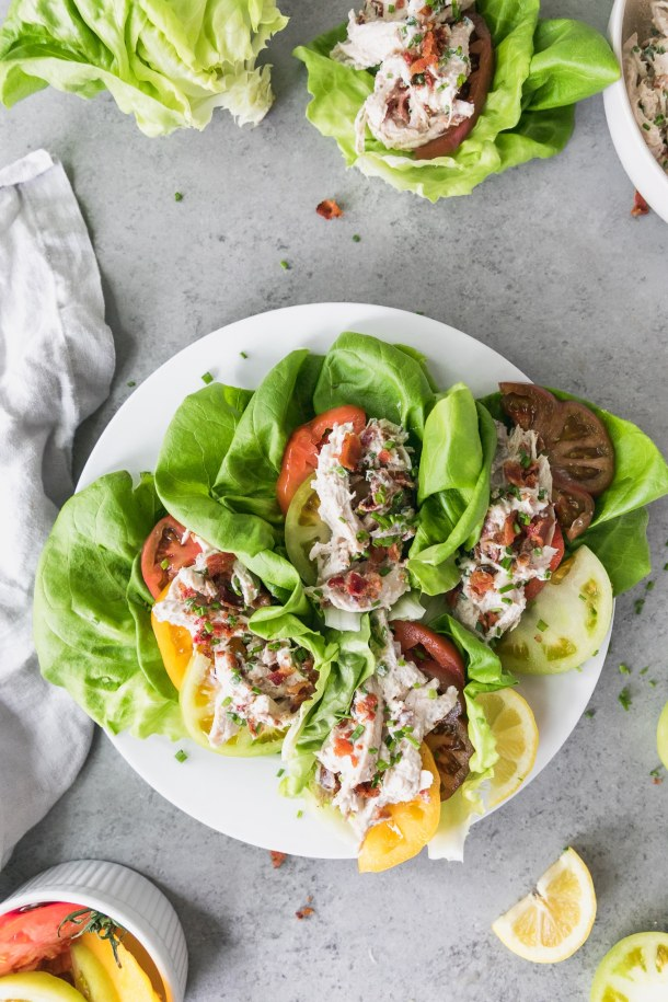 Overhead shot of a white plate with 4 chicken salad lettuce wraps on them with sliced heirloom tomatoes and chopped bacon with lemon wedges off to the side and a bowl of sliced tomatoes in the bottom left of the frame