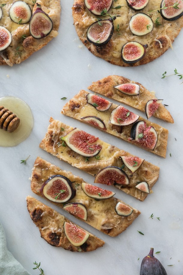 Overhead shot of a fig flatbread sliced into pieces and a honey dipper next to it