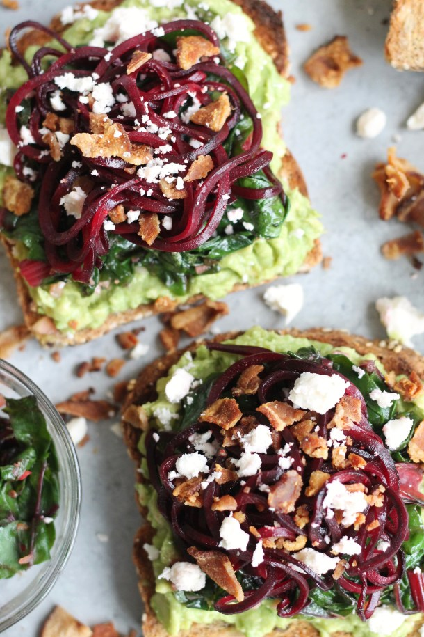 Overhead closeup shot of two slices of avocado toast topped with sautéed swiss chard, spiralized beets, bacon, and feta