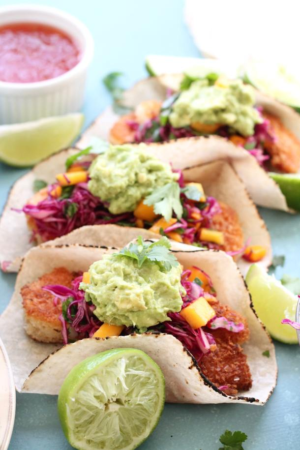 Closeup shot of coconut shrimp tacos with avocado mash, lime, and sweet chili slaw