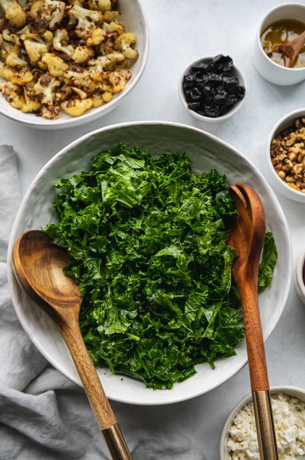 Overhead shot of a bowl of kale with wooden salad servers in the bowl and bowls of ingredients surrounding it