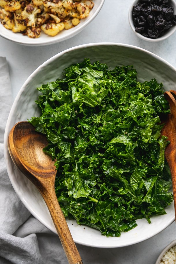 Overhead close up shot of a bowl of kale with wooden salad servers in the bowl