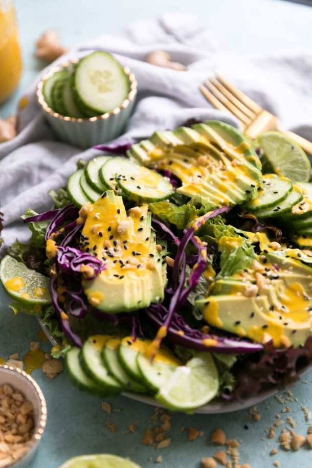 Close up shot of salad topped with sliced avocado, cucumber, carrot ginger dressing, and sesame seeds