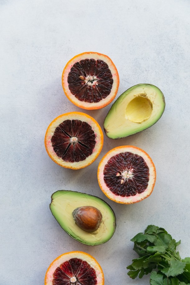 Overhead shot of halved avocados and halved blood oranges
