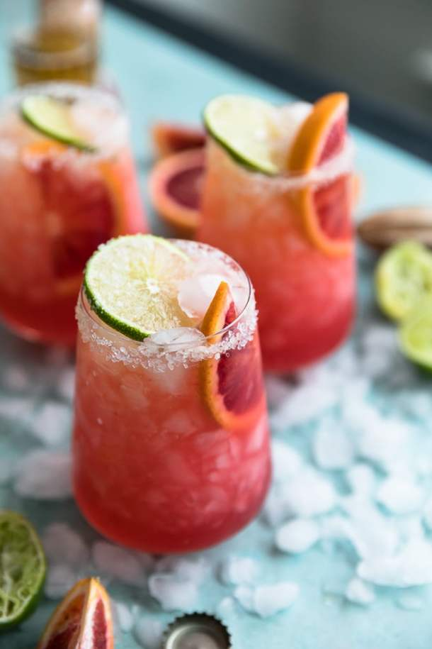 Close up shot of three blood orange beergaritas with crushed ice, lime, and a citrus reamer on a teal background