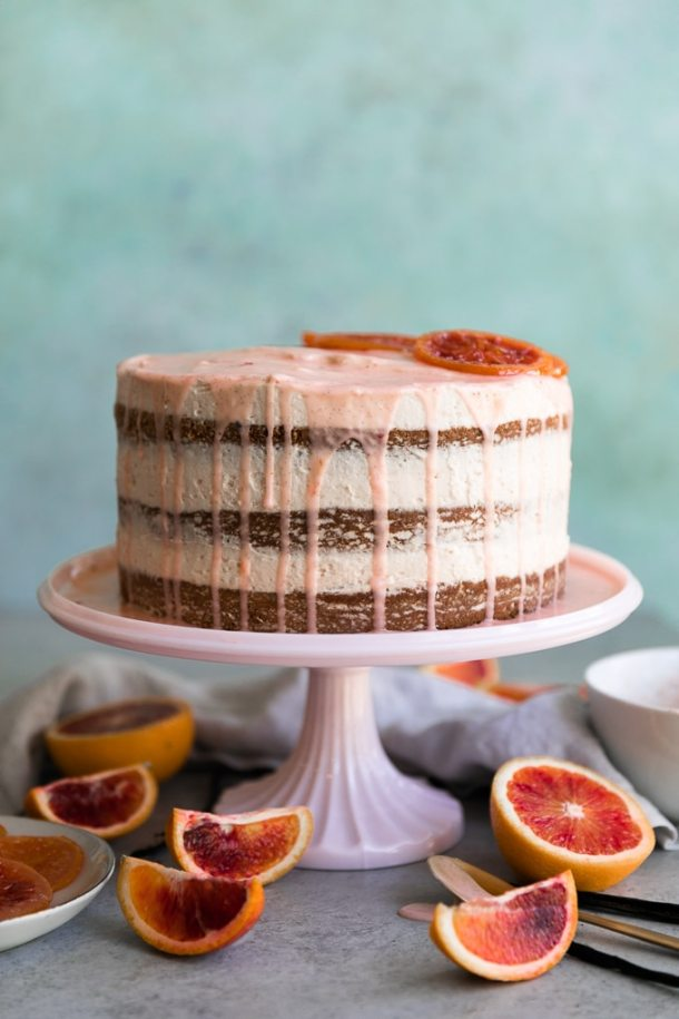 Straight on shot of blood orange layer cake with pink glaze dripping down the sides and candied blood oranges on top