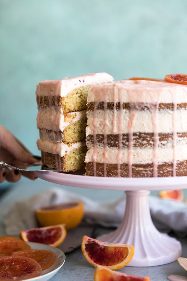 Forward facing close up shot of a blood orange layer cake with pink glaze dripping down and a slice being pulled out
