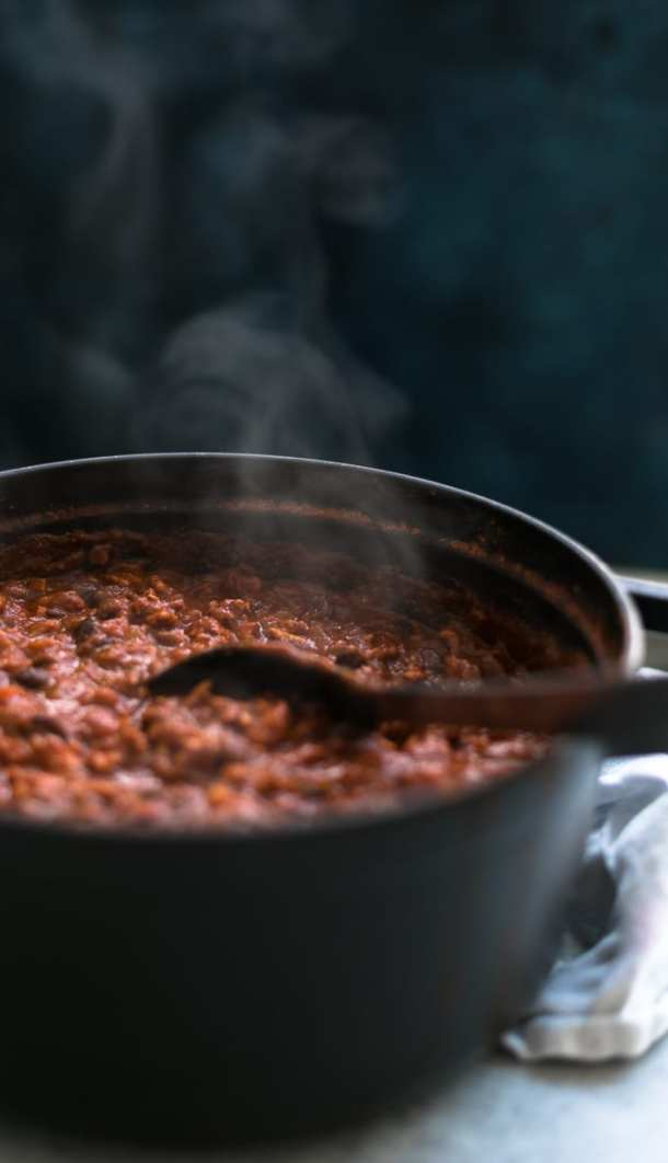 Close up shot of a black dutch oven filled with chili with steam coming out and a rich, dark blue background