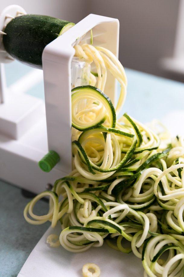 Close up shot of a spiralizer making zucchini noodles