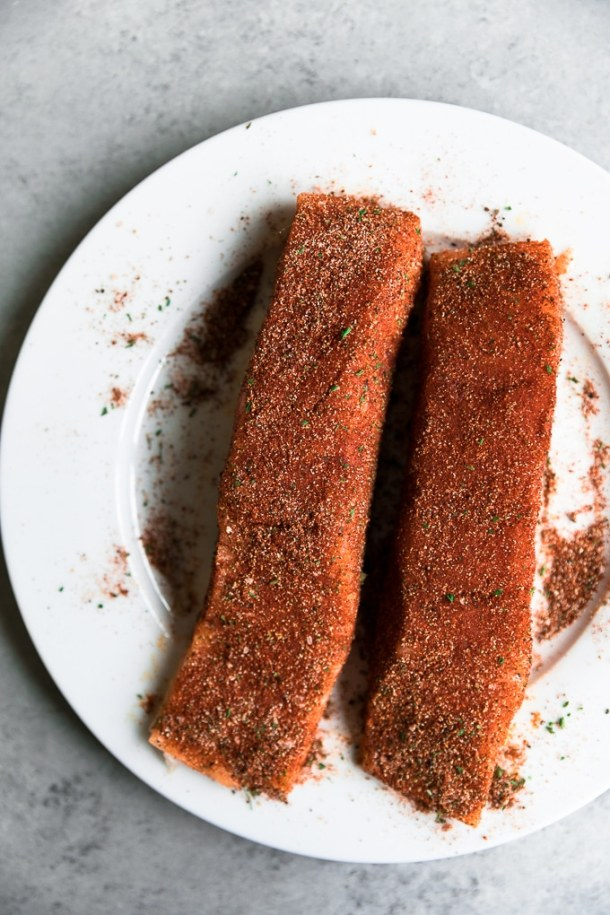 Overhead shot of two salmon fillets rubbed with a spice mixture on a white plate