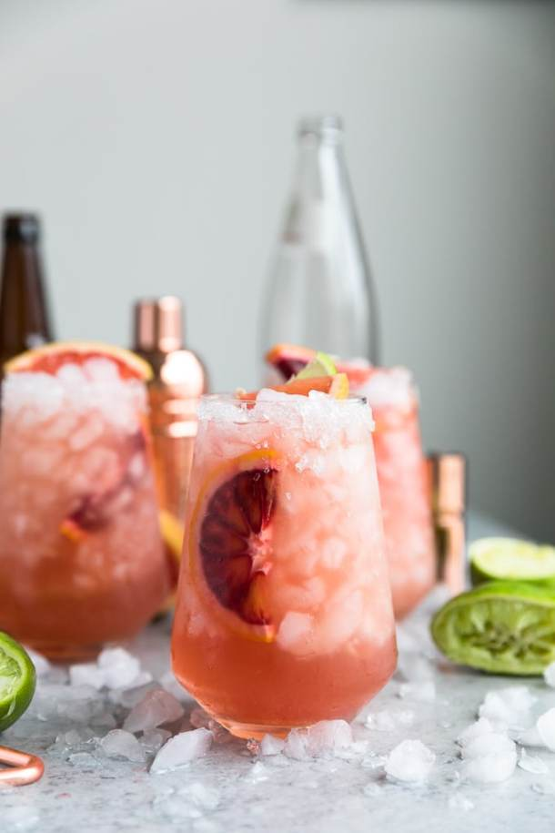 Straight on shot of three pink cocktails with a bronze shaker, beer bottle, and glass bottle in the background with squeezed limes