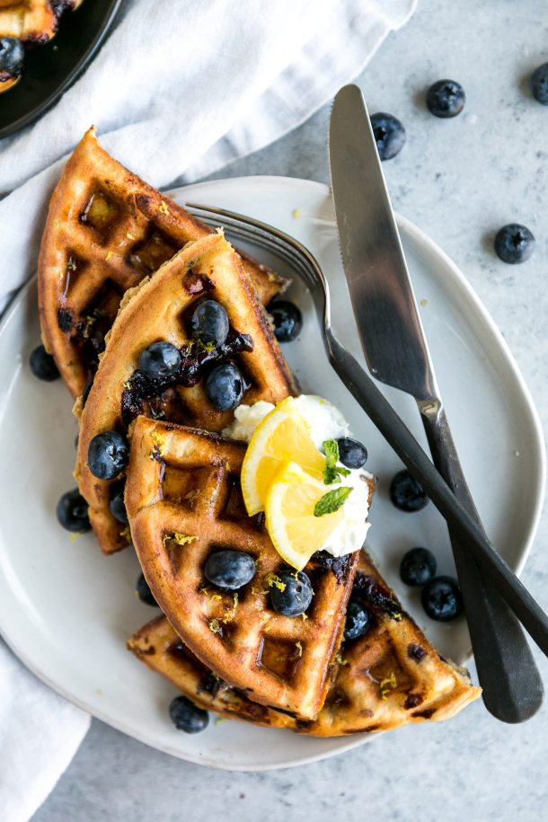 Overhead shot of a waffle cut into quarters topped with blueberries and lemon slices and a fork and knife off to the side