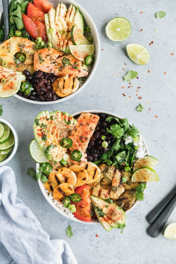 Overhead close up shot of two bowls of salmon with grilled plantains, black beans, grilled pineapple, lime, tomatoes, sliced avocado, and cilantro with lime wedges and herbs scattered around