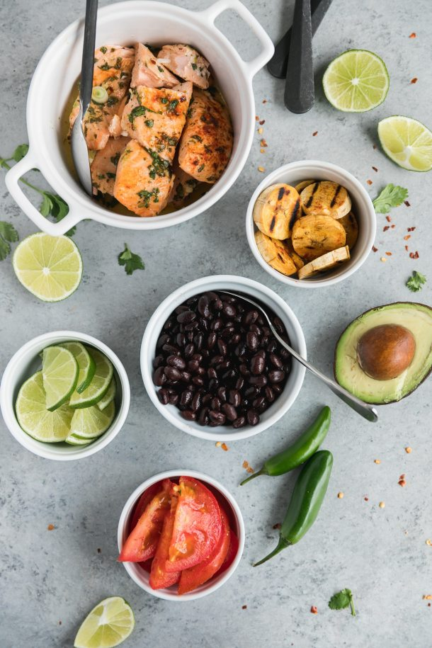 Overhead shot of a bowls of salmon, grilled plantains, avocado, black beans, limes, tomatoes, and a halved lime, halved avocado, and two serrano peppers