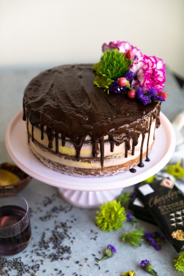 Shot of a layer cake on a cake stand with pastel colored icing, chocolate ganache dripping down the cake, and flowers on top