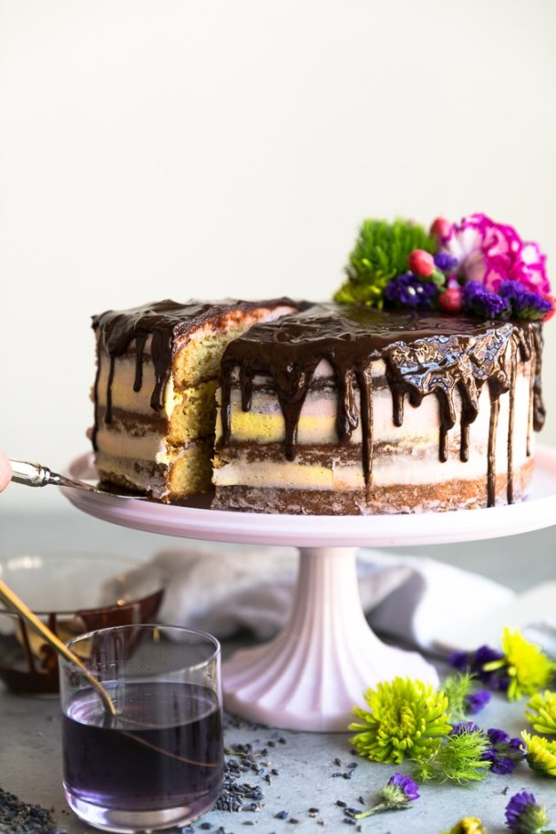 Straight on shot of a layer cake with chocolate ganache dripping down with a slice being pulled out