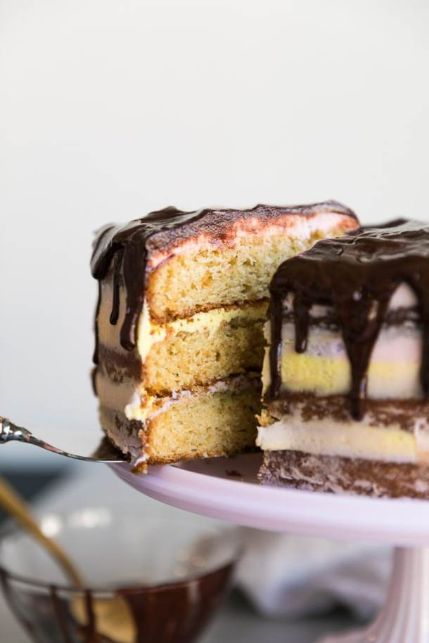 Close up shot of a layer cake with a slice being pulled out