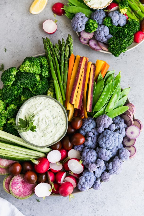 Overhead shot of a veggie platter with broccoli, asparagus, carrots, snap peas, purple cauliflower, radishes, and cucumbers