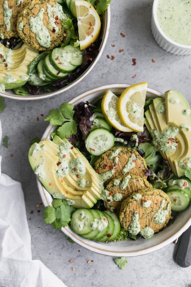 Overhead shot of a salad topped with three falafel, sliced cucumber, sliced avocado, lemon wedges, and a drizzle of yogurt sauce, with another salad peeking out in the top left of the frame, and a bowl of yogurt sauce in the top right
