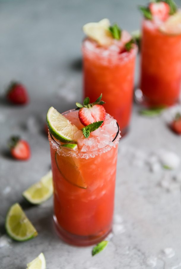 Close up shot of a strawberry margarita with a lime wedge, halved strawberry, and mint leaves sticking out, with two margaritas in the background