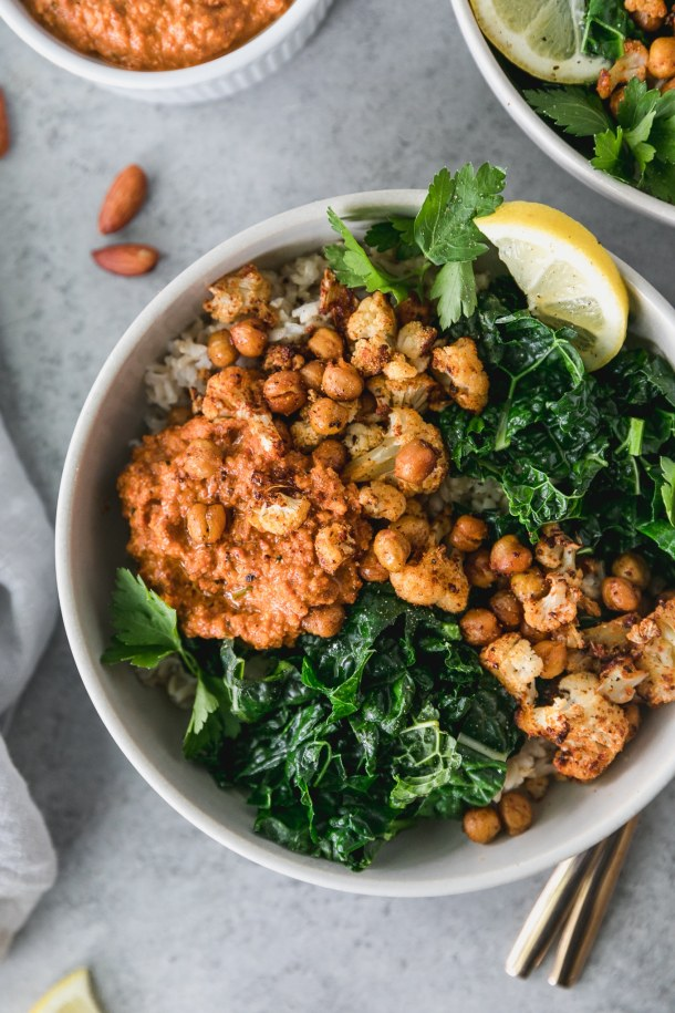 Overhead close up shot of a bowl filled with brown rice, sautéed kale, roasted chickpeas, cauliflower, a scoop of romesco sauce, and a lemon wedge and almonds scattered beside the bowl
