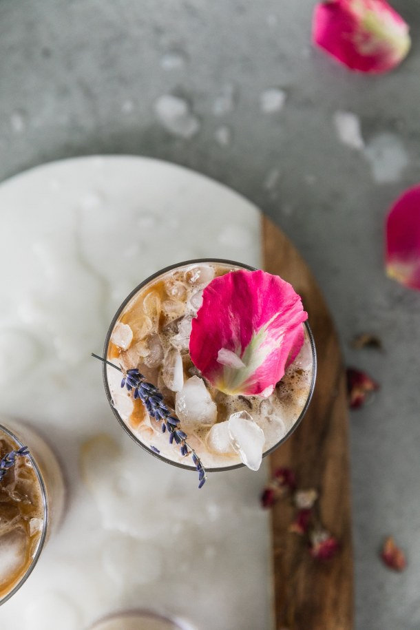 Overhead close up shot of an iced latte topped with a sprig of lavender and a pink rose petal