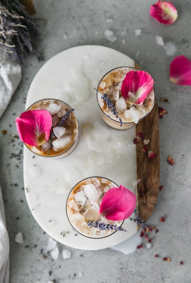 Overhead shot of 3 iced lattes topped with rose petals and lavender sprigs