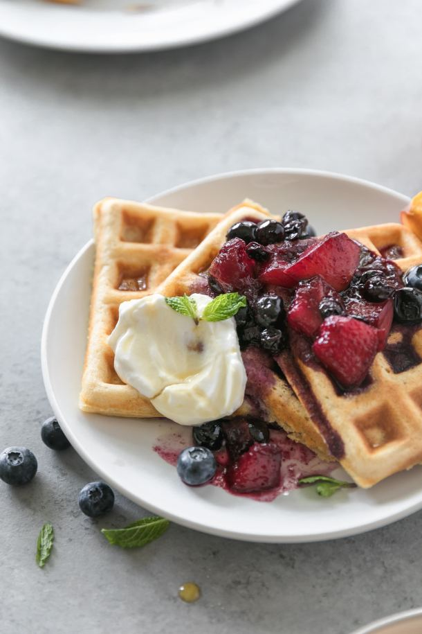 Close up shot of a plate of buttermilk waffles topped with peach blueberry compote and a dollop of Greek yogurt and a sprig of mint