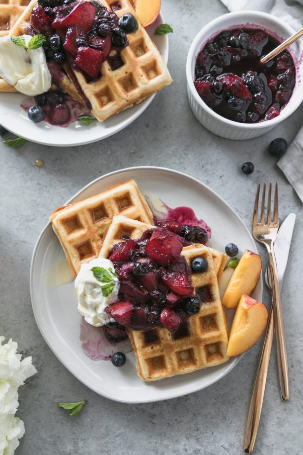 Overhead close up shot of a plate of buttermilk waffles topped with peach blueberry compute, sliced peaches on the side, and a gold fork and knife next to it