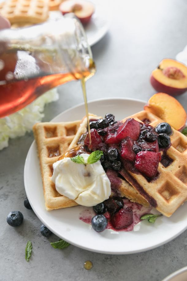 Close up shot of a plate of waffles topped with peach blueberry compote being drizzled with maple syrup