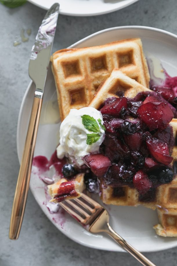 Overhead close up shot of a plate of buttermilk waffles topped with peach blueberry compote, a dollop of greek yogurt, and a sprig of fresh mint