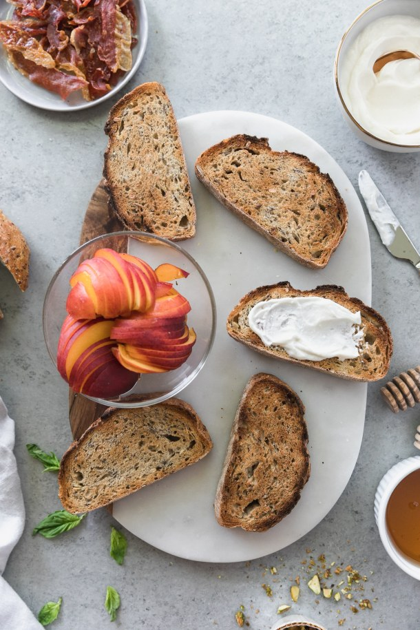Overhead shot of a board topped with 5 slices of toast and a bowl of sliced peaches with a honey dipper, knife, bowl of whipped ricotta, and bowl of honey next to it