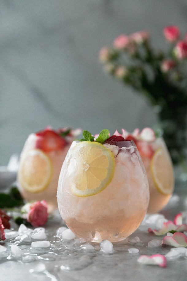 Forward facing shot of a glass of sangria with two glasses behind it, garnished with strawberry slices. lemon, and fresh mint with flowers in the background and rose petals scattered around