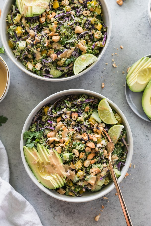 Overhead shot of a salad with cashews, avocado, lime wedges, and a gold fork sticking out of the bowl