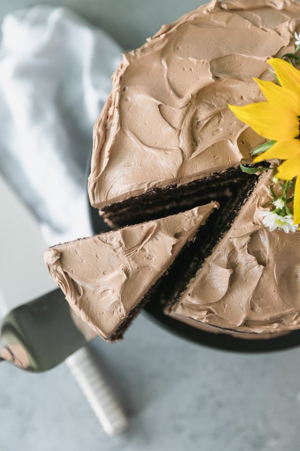 Overhead close up shot of a piece of chocolate cake being taken out from the cake