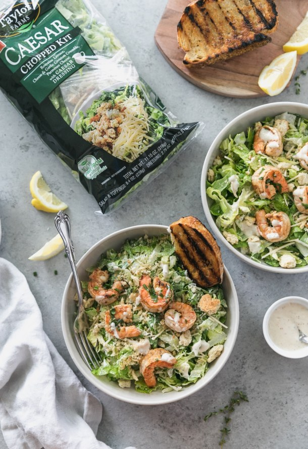 Overhead shot of two caesar salads with shrimp and garlic bread and a bag of packaged salad off to the left