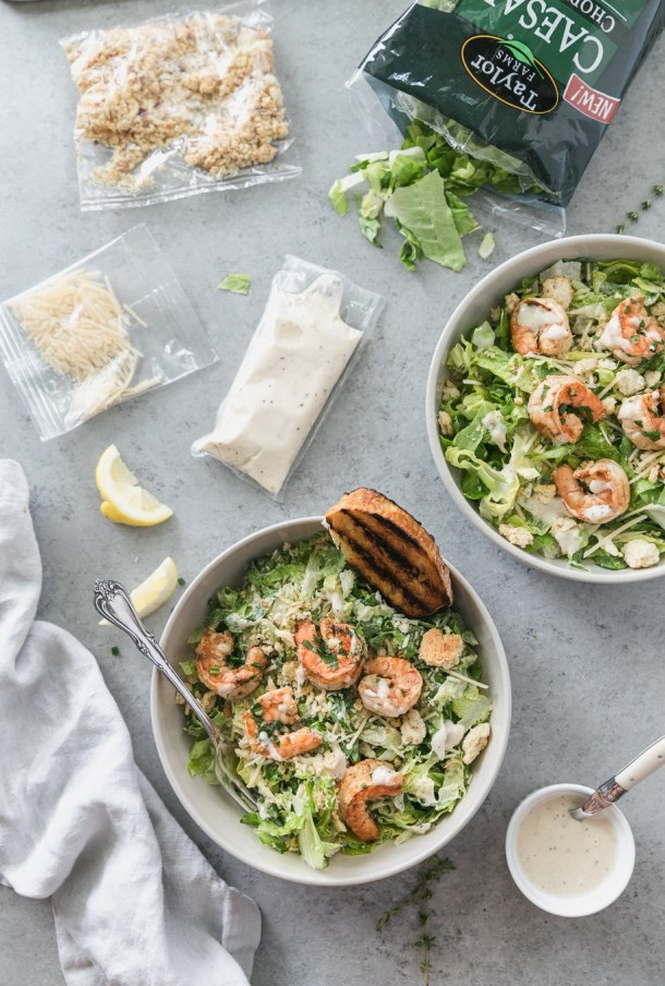 Overhead shot of two shrimp caesar salads with packets of dressing, parmesan, croutons, and lemon wedges scattered above