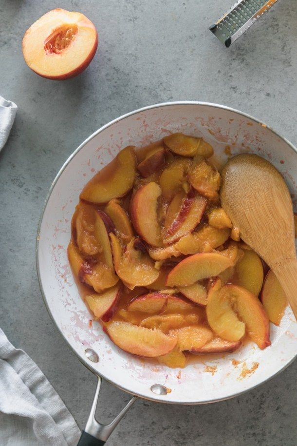 Overhead shot of a skillet filled with sautéed peaches with a wooden spoon in the skillet