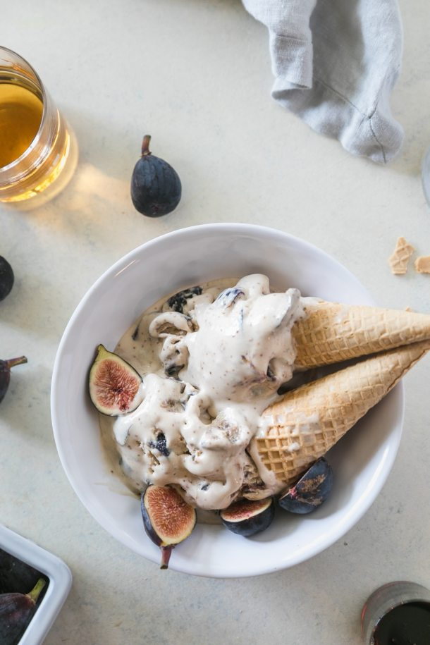 Overhead shot of two half melted ice cream cones in a bowl with fresh figs and a glass of bourbon off to the side