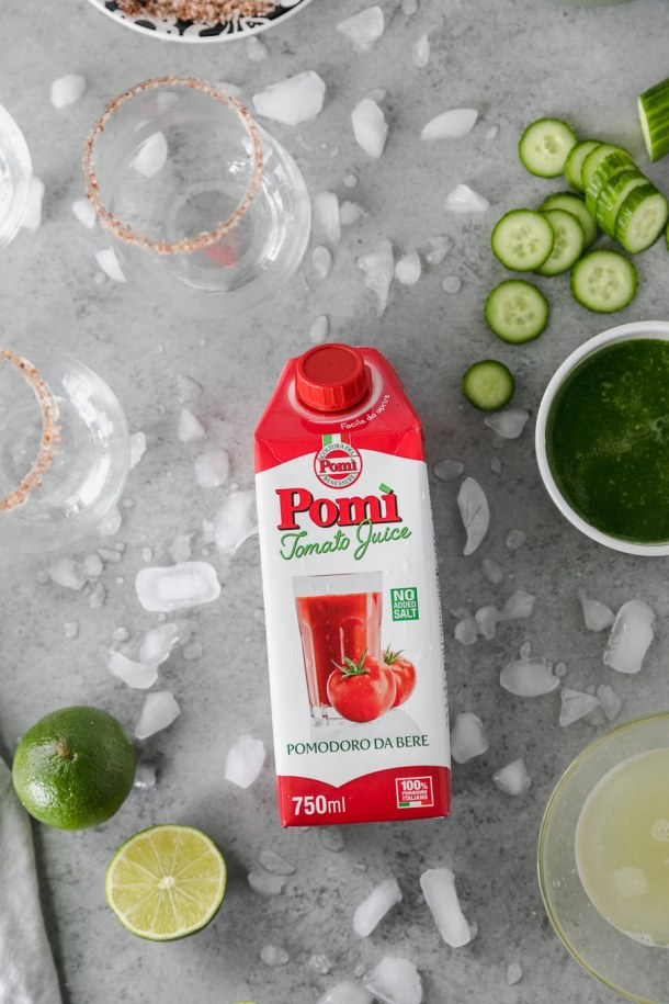 Overhead shot of a carton of tomato juice surrounded by crushed ice, sliced cucumbers, cucumber juice, and rimmed glasses
