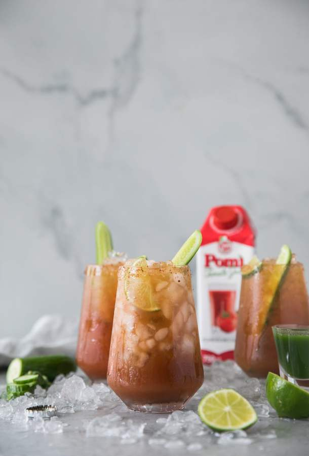 Forward facing shot of 3 michelada cocktails with lime wedges and cucumbers sticking out of them, with a carton of tomato juice in the background and crushed ice scattered around