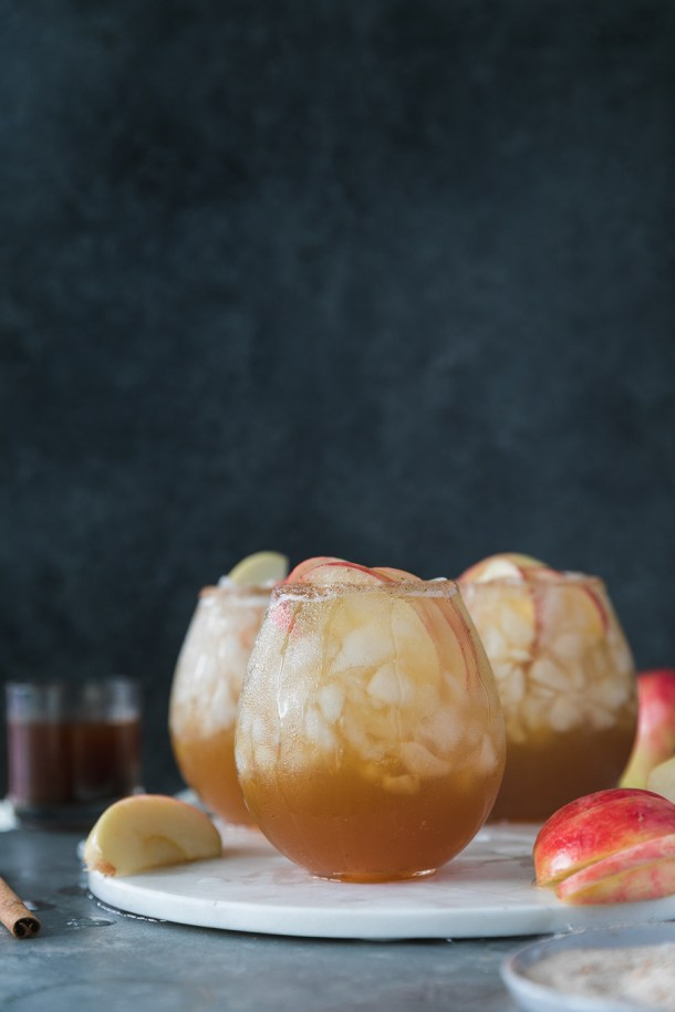 Forward facing shot of apple pie bourbon fizz cocktails on a marble board with a dark blue background and sliced apples and cinnamon sticks off to the side