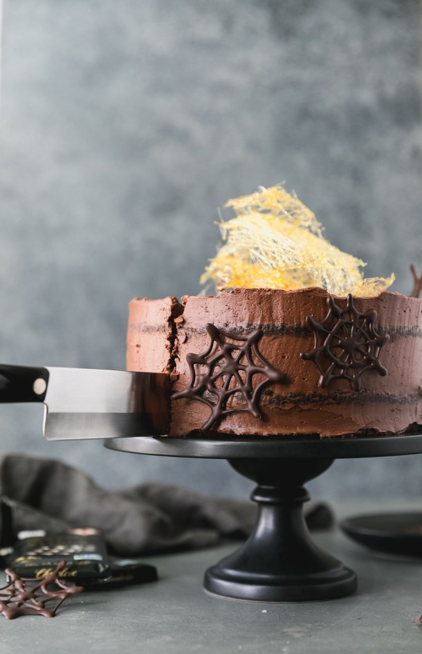 Forward facing shot of a large knife cutting into a chocolate cake with dark chocolate spider webs on it and a spun sugar cobweb on top