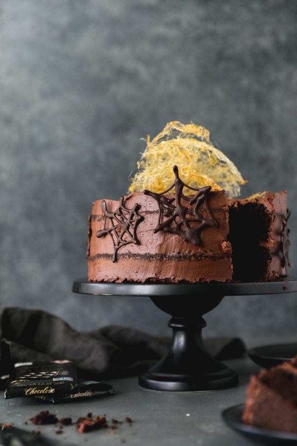 Forward facing shot of a chocolate cake with chocolate spider webs on it and a spun sugar web on top with a piece taken out of the cake
