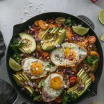 Overhead shot of a black skillet filled with chilaquiles, fried eggs, avocado, cilantro, and tomatoes