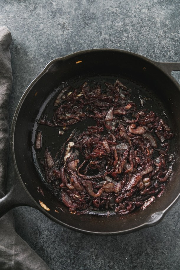 Overhead shot of a black cast iron skillet filled with red wine caramelized onions