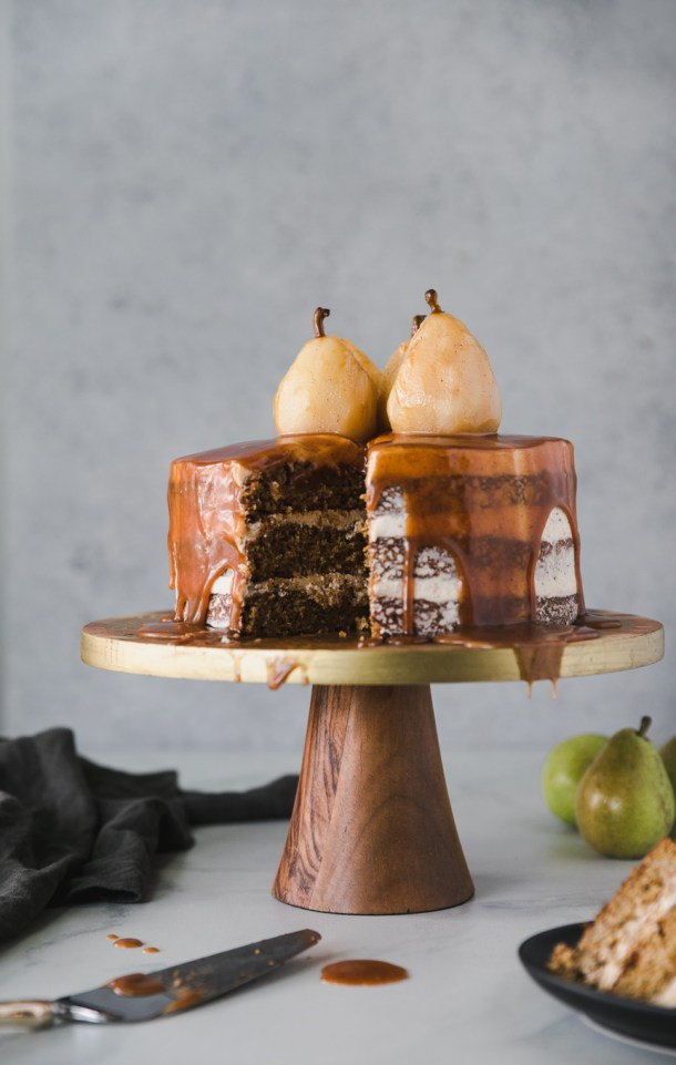 Forward facing shot of a layer cake dripping in caramel sauce, topped with poached pears on a gold and wooden pedestal