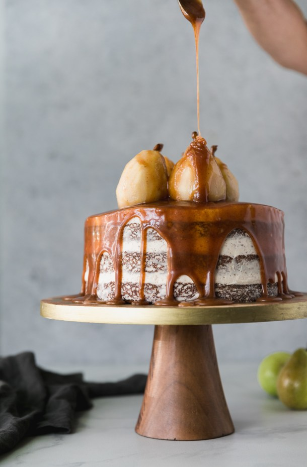 Forward facing shot of a cake on a wooden and gold pedestal topped with poached pears, being drizzled with caramel sauce