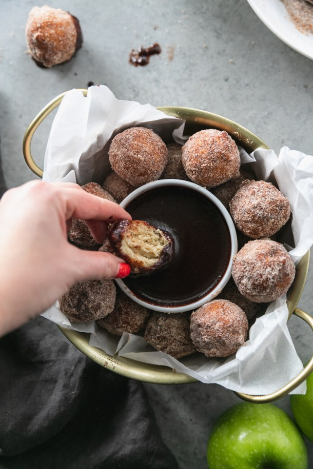 Overhead close up shot of a gold bowl with handles filled with doughnut holes and a hand dipping a doughnut hole into dark chocolate fudge sauce